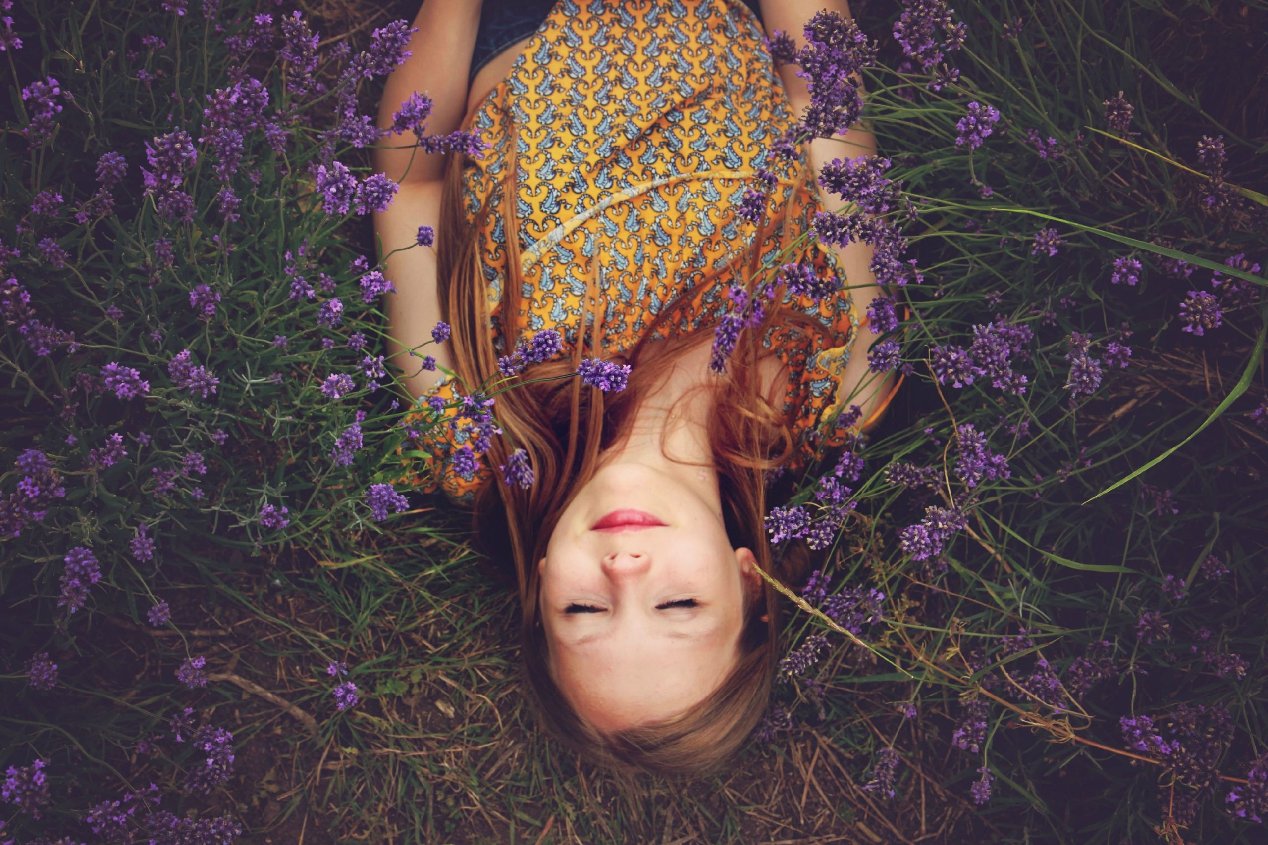 woman in yellow and teal top sleeping beside lavenders
